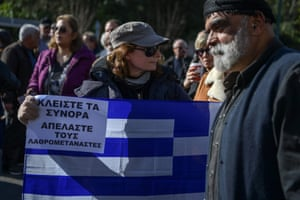 A woman holding a Greek flag protests against the country's refugee camps