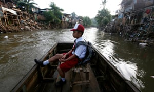 A boy sits in a wooden boat transporting him across a river to go to school in Jakarta