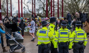 Met police officers look on as people leave floral tributes at the bandstand on Clapham Common.