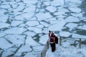 A pedestrian stops to take a photo by Chicago River as bitter cold phenomenon called the polar vortex has descended on much of the central and eastern United States.