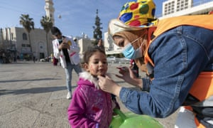 A Palestinian volunteer paints a child's face at Manger Square, in the Church of the Nativity, ahead of scaled-back celebrations for Eastern Orthodox Christmas due to the coronavirus pandemic, in the West Bank city of Bethlehem, Tuesday, 5 January, 2021.
