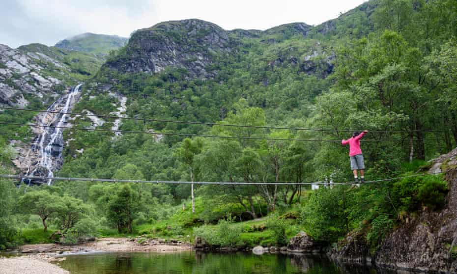 Woman walking across the An Steall wire bridge over the Water of Nevis river with Steall Falls beyond, in Scotland, UK.