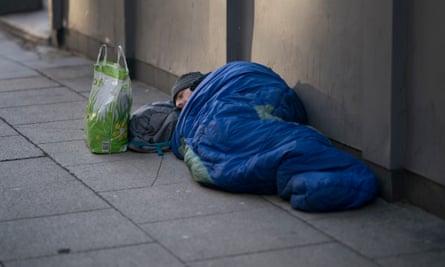 Homeless man in sleeping bag on street