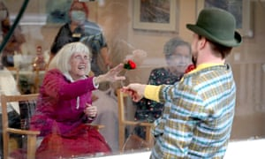 Residents watch a comedy performance through a window at Spring Lane nursing home in north London