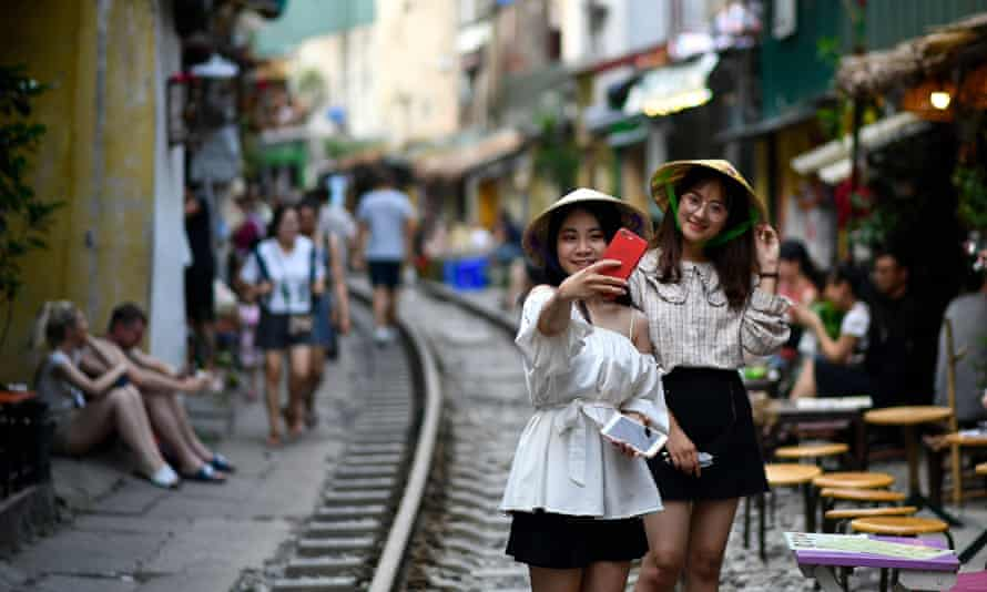 Tourists posing for a selfie on the railway track in Hanoi's popular train street.