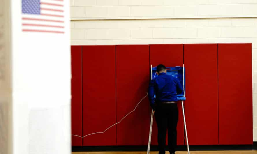 A voter completes his ballot inside a privacy booth at a polling station inside Knapp elementary school on election day in Racine, Wisconsin, 3 November.