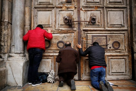 Worshippers kneel and pray in front of the closed doors of the church