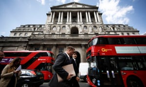 Businessmen pass red London buses outside the Bank of England in the City of London.