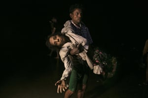 Sona Banu is carried by Nobi Hossain to the shore of the Naf river as hundreds of Rohingya arrive by boats in the safety of darkness.