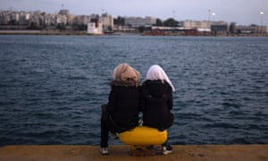 Two women from Syria sit facing the sea at Piraeus harbour in Athens, Greece.