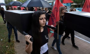A young Israeli woman carries a coffin during a protest held by family members and friends of women killed by violence in Tel Aviv, Israel.