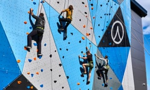 Climbers scaling the outdoor climbing wall at Adventure Parc Snowdonia