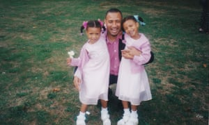 Shannon and Cheriece Hylton as infants, dressed identically in pink dresses, with their father Dwight.