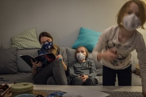 Eva Ciesielska reads to her daughters Zoe (centre), nine, and Lena, six