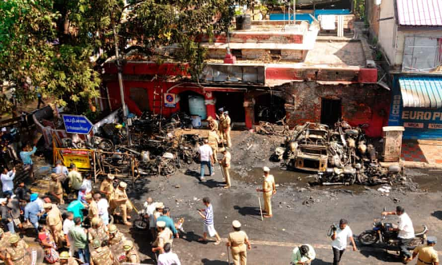 Crowds gather at the scene where vehicles were set ablaze in front of a police station in Chennai