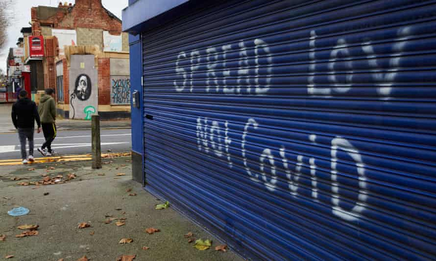"""Residents passing graffiti reading """"Spread Lov [sic] Not Covid"""" in Gipsyville, the ward with the highest Covid-19 infection rate in Hull."""