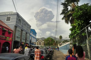 People look at the erupting volcano