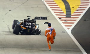 A track marshall runs to collect debris after Force India's Nico Hülkenberg crashed at the start of Sunday's Singapore Grand Prix.