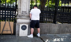 A far right protester urinates on the memorial to PC Keith Palmer outside the Houses of Parliament.