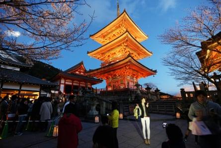 Visitors pose next to a pagoda outside the Kiyomizu-dera temple in Kyoto.