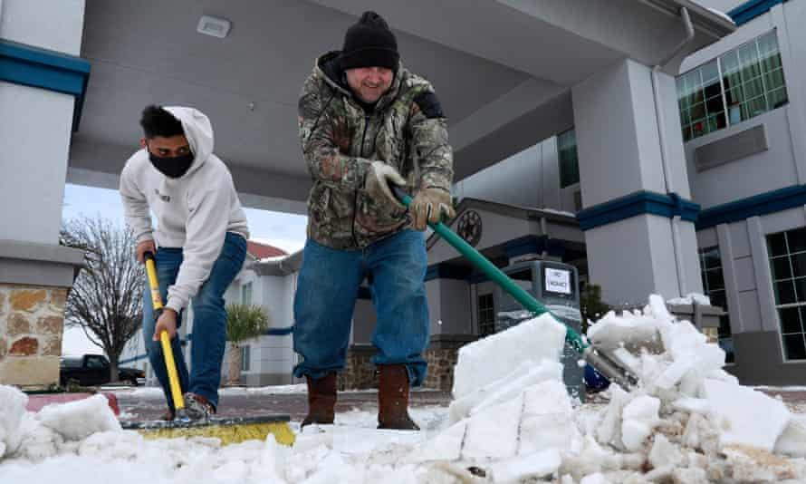 Sam Patel (L) and Mike Bollin (R) clear snow from the front of the SureStay Plus Hotel which is completely full with guests that have no power at home, in Benbrook, Texas, 16 February 2021.