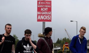 People walk past a poster calling for an Irish language act in Belfast, Northern Ireland