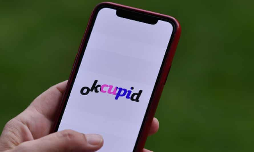 A person looks at the OkCupid dating app on a smartphone.