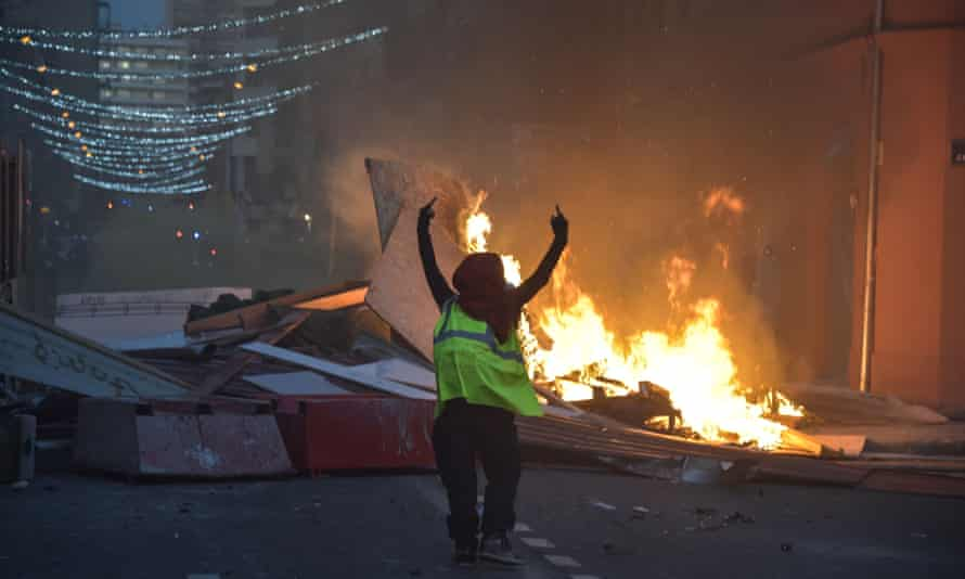 A gilet jaune demonstrator gestures in front of a burning barricade in Toulouse.