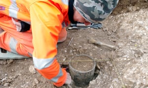An archaeologist excavates a bronze age vessel found during preliminary work on the A303 tunnel under Stonehenge.