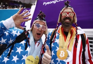 Bitcoin logos and stars and stripes as these USA fans wait for the short track speed skating quarter-finals