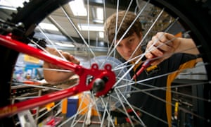 A bicycle mechanic works on a bike at a Halfords store