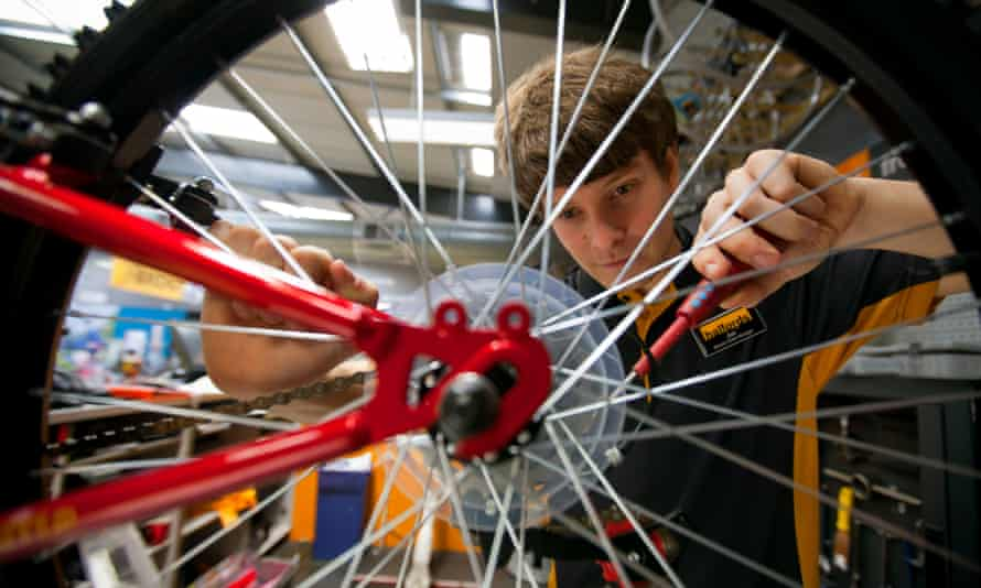 A Halfords employee fixes a bicycle