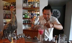 Barman Raka Ambarawan pours a cocktail at the Night Rooster bar.