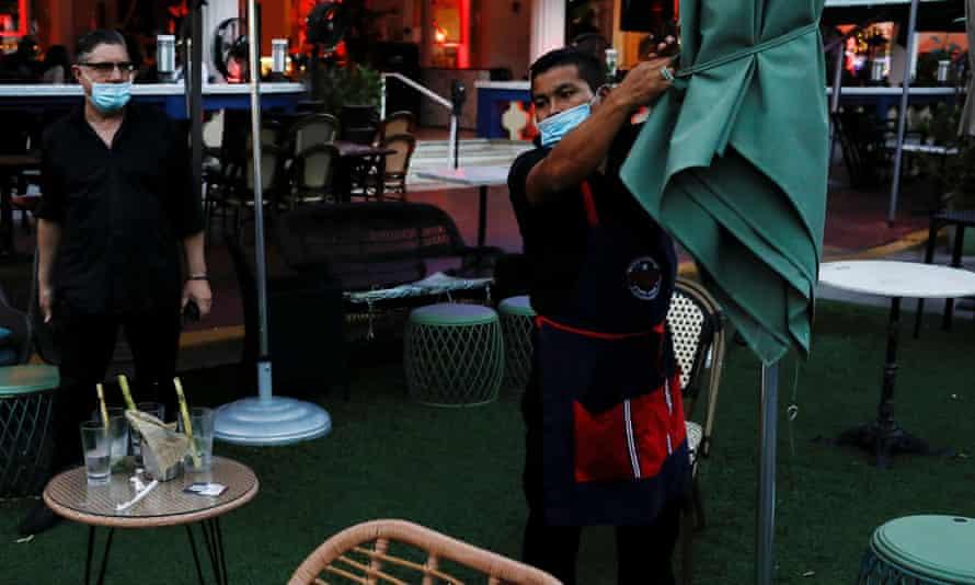 A man closes a restaurant ahead of an 8pm curfew.