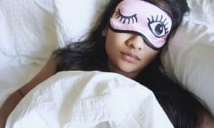 A woman wears an eye mask while sleeping.