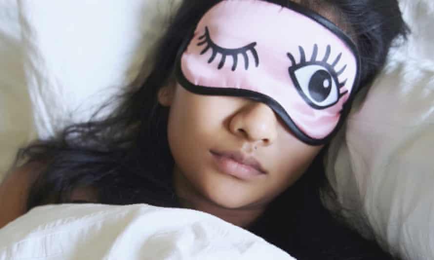 Woman Wearing Eye Mask While Sleeping In Bed