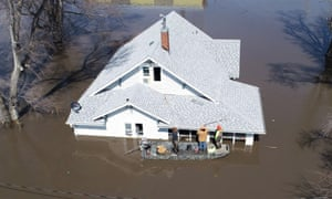 A team enters a flooded house to pull out several cats during flooding of the Missouri river near Glenwood, Iowa on 18 March.