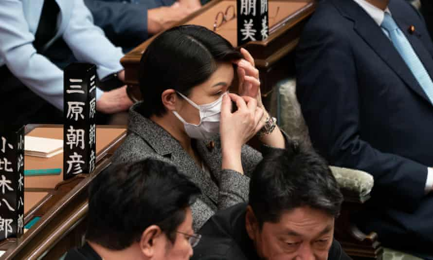A member of the Japanese house of representatives, in Tokyo, adjusts her face mask during a session on 27 February.