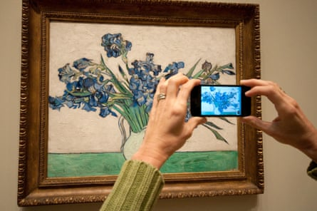 A woman snaps a photo of Iris by Vincent Van Gogh at the Metropolitan Museum of Art in New York.