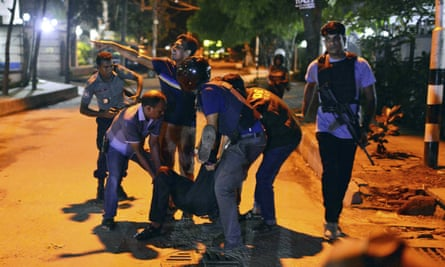 People help an unidentified injured person after a group of gunmen attacked a restaurant popular with foreigners in a diplomatic zone of the Bangladeshi capital Dhaka.