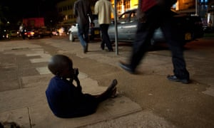 A young child begs on the pavement in Kampala
