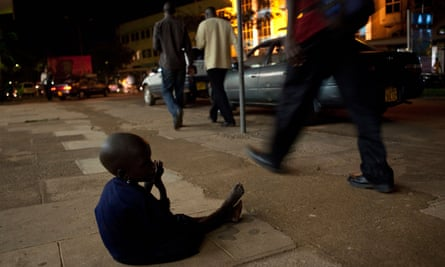 A young child begging on the pavement as pedestrians walk by