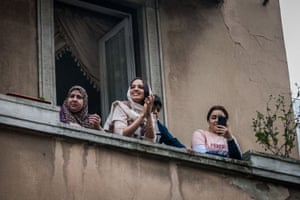 People play applaud and sing from the balconies in Via Mameli in Milan, norther Italy