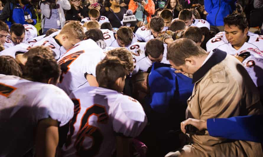 Players pray before a game in Bremerton, Washington