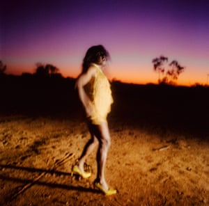 Matthew Thorne - Derik Lynch Dancing in Drag on Inmar Ground in Pastel (Aputula, Central Australia) From the series The Australians October 2019 Derik Lynch is a Yankunytjatara man whose land is the remote north west of South Australia, also known as the APY lands. An initiated indigenous man, he is an openly queer artist, performer and dancer. Having started singing and dancing aged five, Lynch appeared in the acclaimed theatre production Namatjira and travelled with the play for its presentation at the Southbank Centre in London. The image was taken by Thorne during the making of Dipped in Black a film and photographic project undertaken as a collaboration with Lynch exploring his childhood growing up in the Central Desert of Australia in dream and memory. Thorne explains that part of its significance: 'This photo was taken as Derik danced drag on sacred Inmar ground for his mob, the first time this has been done to our knowledge in 65,000yrs+ of indigenous history'.