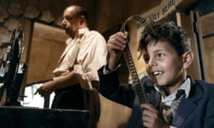 Salvatore Cascio as the child Salvatore 'Toto' Di Vita in the film Cinema Paradiso holds up a strip of film reel looking closely at it, his face lit up with a broad smile. The middle aged Philippe Noire is in the background