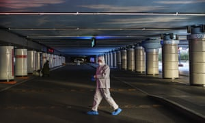A Chinese railway worker wears a protective suit as he walks across empty taxi lanes at Beijing West Railway Station on 16 February.