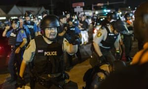 St Louis County police officers interact with anti-police demonstrators during protests in Ferguson, Missouri August 10, 2015.