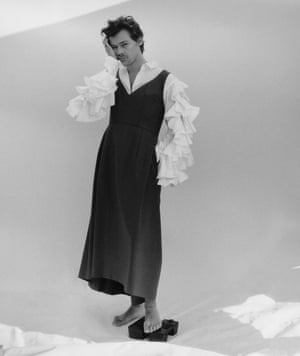 Harry Styles wearing a pinafore dress and shirt with ruffled sleeves by Comme des Garçons