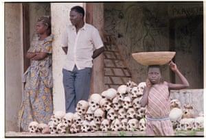 Ugandans standing near human skulls, 1986